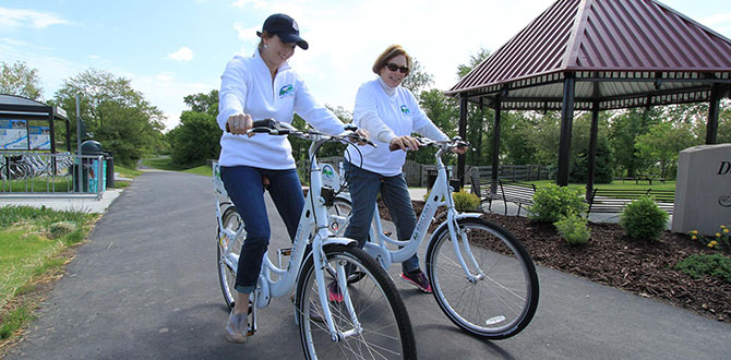 Two women riding River Cities Bike Share Program bikes along the Dearborn Trail near Aurora, Indiana.