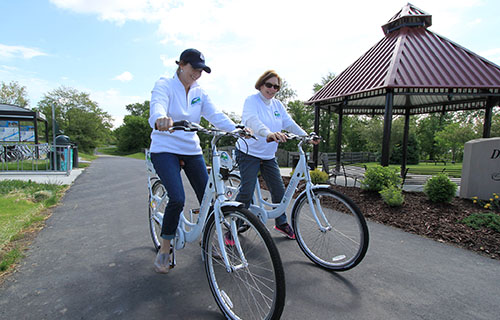 Two ladies riding distictive River Cities Bike Share bikes on the Dearborn Trail